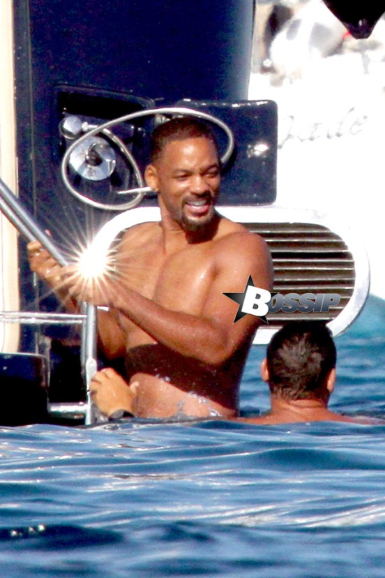 Actor Will Smith having fun in the sun with a boat full of friends where he is cheered on by the group a then he jumps off his boat into the water on lovely vacation in Formentera.